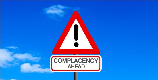 Complacency ahead warning road sign