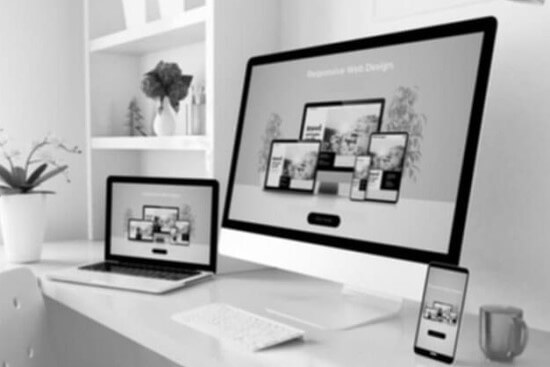 Black and white image of an iMac, Macbook and iPhone, all displaying the same website, showing responsive functionality